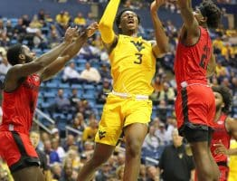West Virginia forward Gabe Osabuohien (3) splits Austin Peay's Antwaun Butler (4) and Terry Taylor (21) for a shot