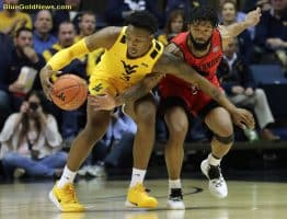 West Virginia forward Gabe Osabuohien (3) wins a fight for a loose ball
