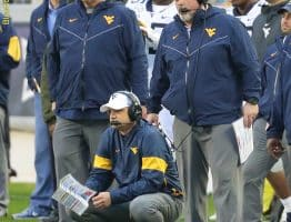 West Virginia coaches Neal Brown (bottom), Matt Moore (right) and analyst Ron West (left) watch a play