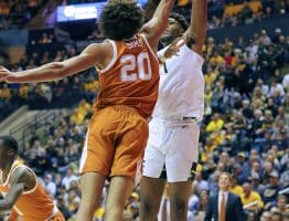 West Virginia forward Derek Culver extends to get a shot over the reach of Texas' Jericho Sims (20)
