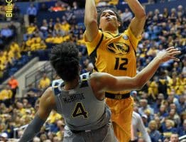 West Virginia guard Deuce McBride (4) takes a charge from Missouri's Dru Smith (12)