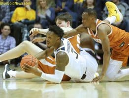 West Virginia forward Gabe Osabuohien (3) wins a floor battle for a loose ball against Texas