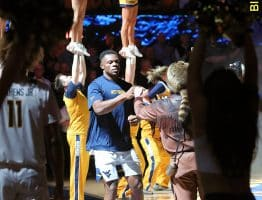 Outlined by dance teamers and cheerleaders, Oscar Tshiebwe is greeted by Mountaineer Timmy Eads on the carpet