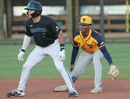 West Virginia shortstop Tevin Tucker fakes a pickoff move behind Coastal Carolina's Cooper Weiss (7)