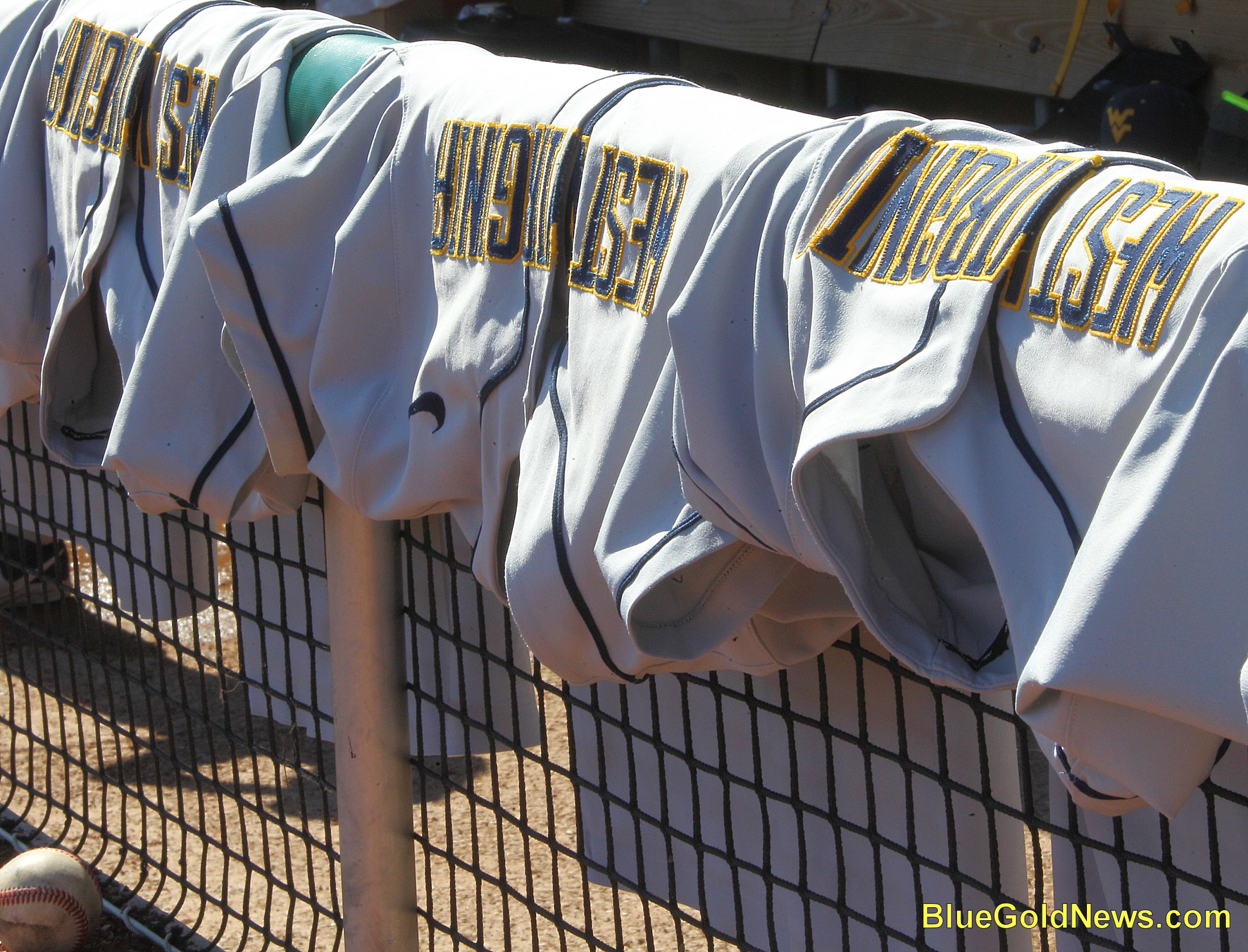 West Virginia uniforms line the dugout railing prior to the game