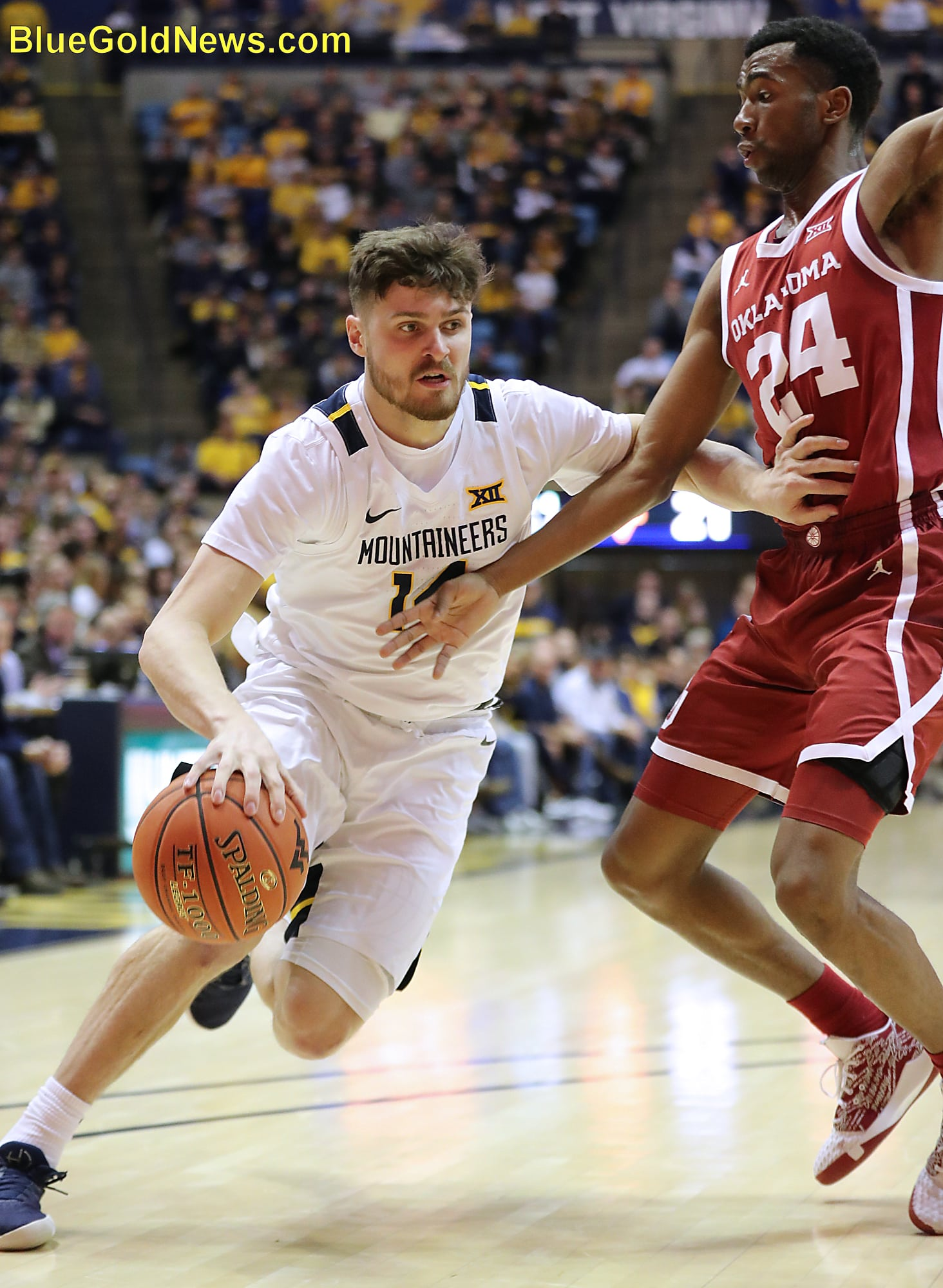 West Virginia guard Chase Harler tries to create room on a drive against Oklahoma's Jamal Bieniemy (24)