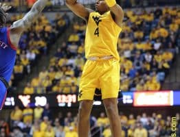 West Virginia guard Deuce McBride (4) hits a jumper over Kansas' Marcus Garrett
