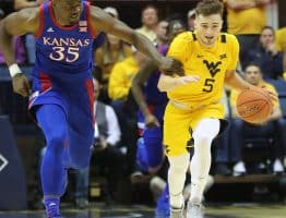 West Virginia guard Jordan McCabe (5) is held by Kansas' Ucoka Azubuike (35). No foul was called on the play.