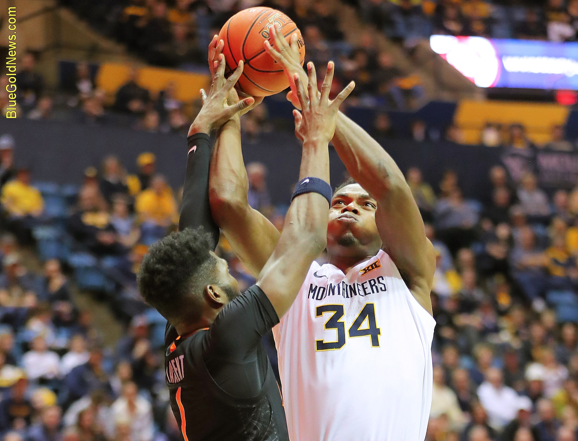 West Virginia forward Oscar Tshiebwe (34) is fouled on a shot attempt by Oklahoma State's Jonathan Laurent (1)