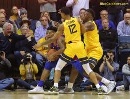 West Virginia's Taz Sherman (12) and Oscar Tshiebwe (back) trap a Kansas ballhandler