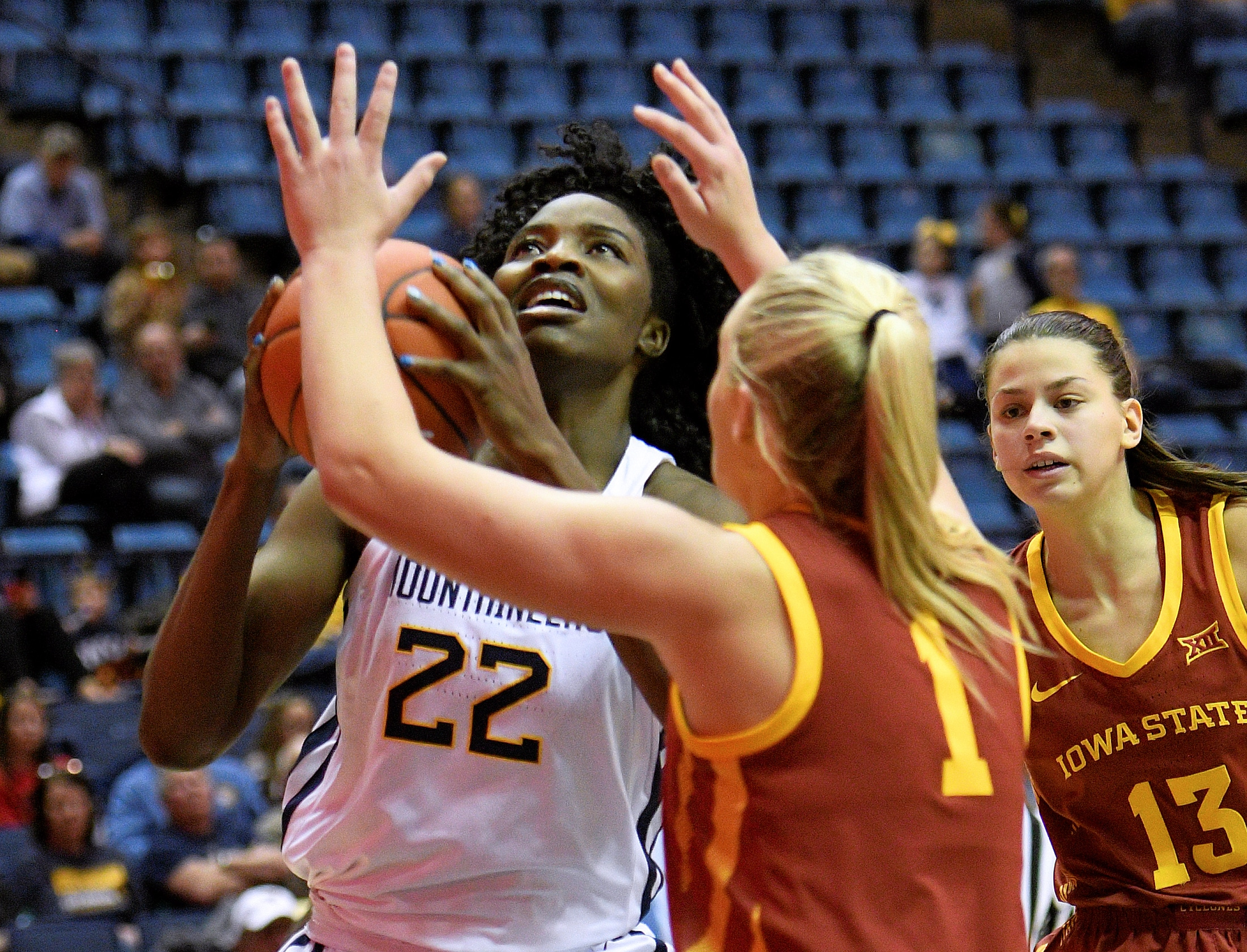 West Virginia center Blessing Ejiofor (22) goes up for a shot over Iowa State's Madison Wise (1)
