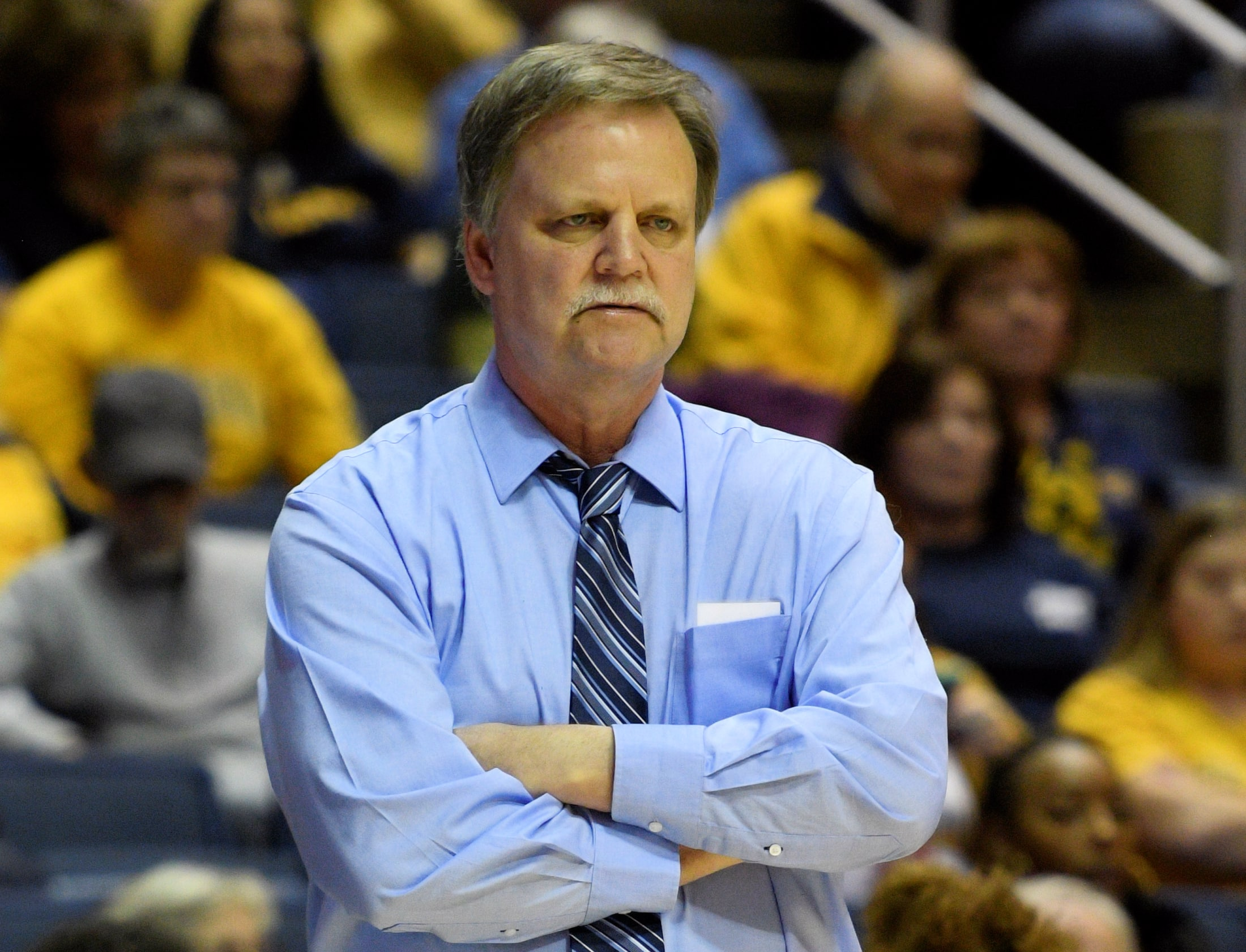 West Virginia head coach Mike Carey studies the court