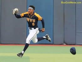 West Virginia outfielder Victor Scott's hat goes flying as he tracks down a fly ball